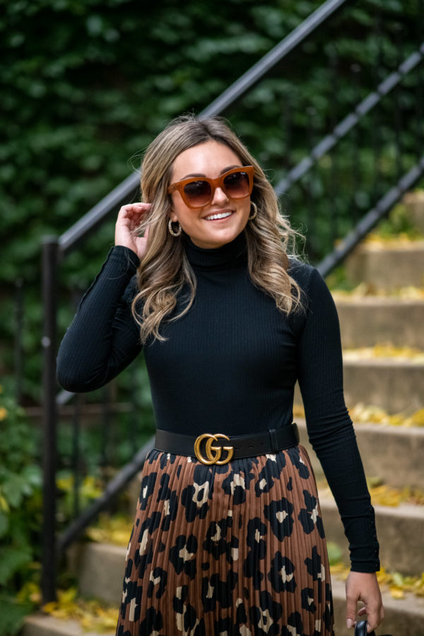 Chicago personal stylist Jessica Sturdy styling Quay brown sunglasses with a black turtleneck and leopard print skirt.