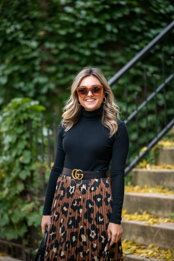 Chicago blogger Bows & Sequins styling a black turtleneck with a pleated skirt and Gucci belt.