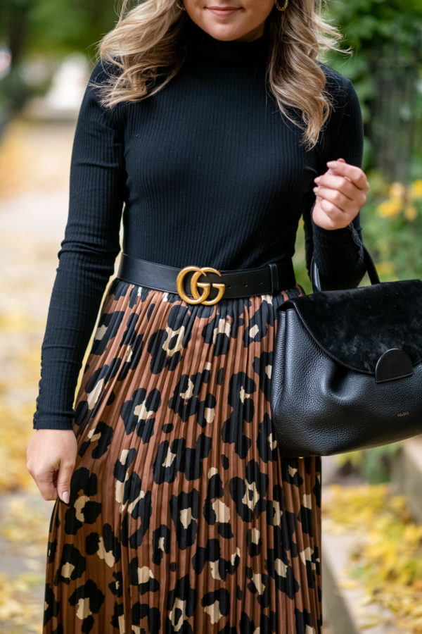 Chicago fashion influencer Bows & Sequins styling a black turtleneck with a leopard skirt.