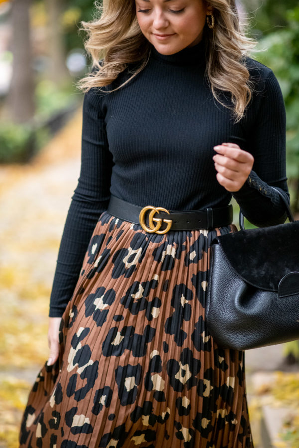 Fashion blogger wearing a black bodysuit with a Gucci belt and pleated skirt.