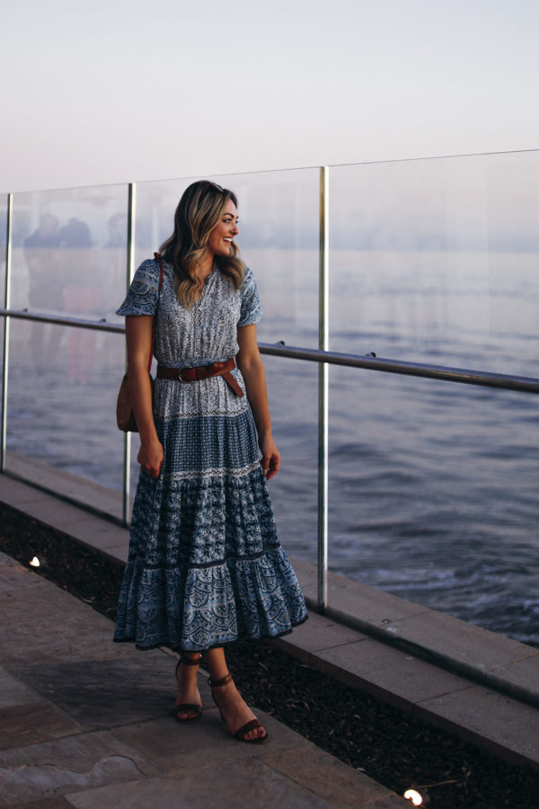 Fashion and travel blogger Jessica Sturdy of Bows & Sequins at Coral Casino in Santa Barbara at sunset. She's wearing a blue printed midi dress by Sea New York, Marc Fisher croc embossed sandals, a leather belt, and a round rattan handbag.