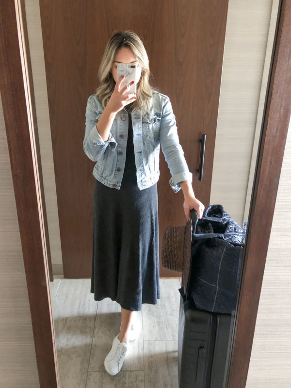 Travel blogger Bows & Sequins wearing a long ribbed sweater dress with a denim jacket and white sneakers with an Away suitcase and MZ Wallace travel bag.