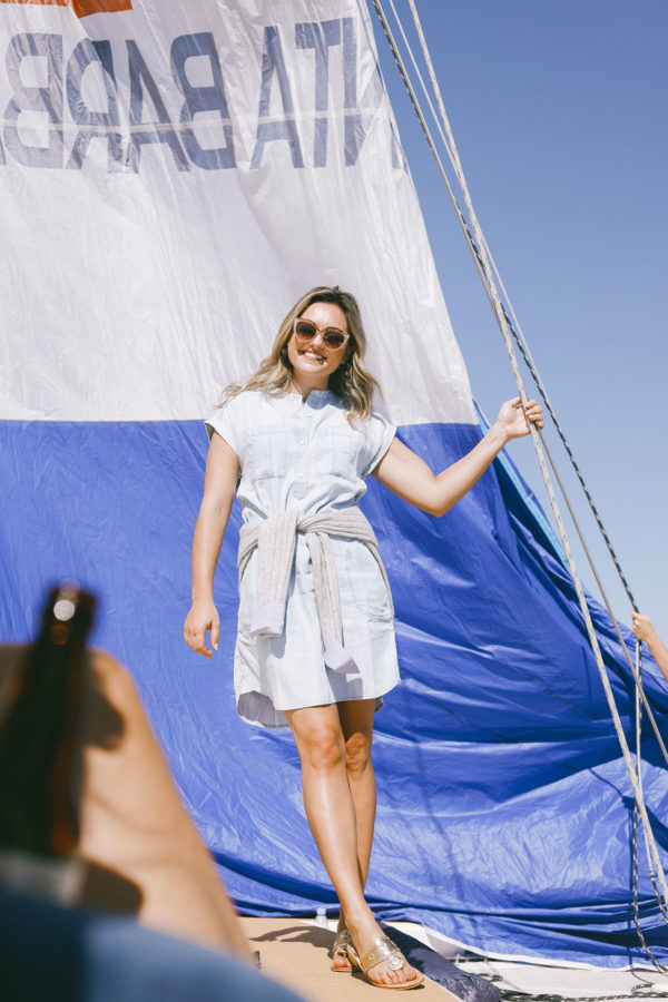 Preppy fashion and travel influencer Jessica Sturdy of Bows & Sequins wearing a Vineyard Vines chambray dress with a cashmere cable knit sweater on a sailboat in Santa Barbara, California.