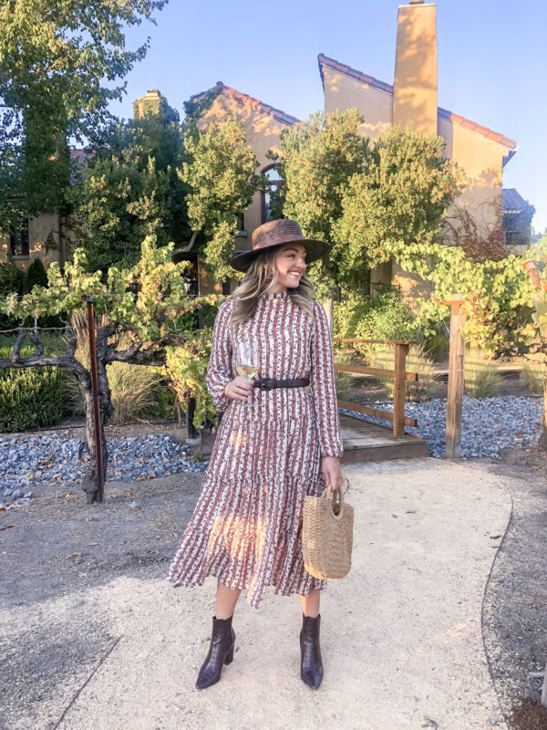 Fashion and travel blogger Jessica Sturdy wearing a long sleeve midi dress with dark brown croc boots, a brown waist belt, and a dark brown straw hat in the vineyard at Vintners Inn Resort for dinner.