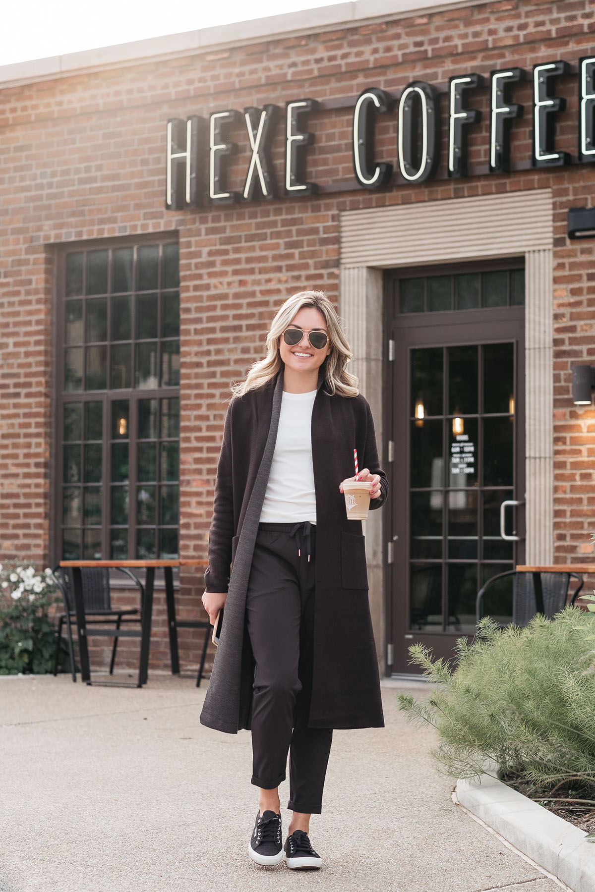 Chicago lifestyle influencer Jessica Sturdy of Bows & Sequins wearing women's jogger pants, Superga sneakers, and a Calia by Carrie Underwood long duster cardigan at Hexe Coffee.