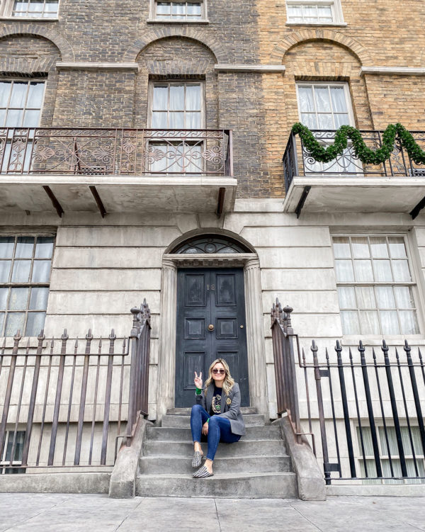 Travel blogger Bows & Sequins sitting on the steps of 12 Grimmauld Place at the Wizarding World of Harry Potter