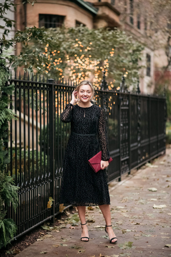 Fashion and beauty blogger Bows & Sequins styling a classic black dress for a holiday party.