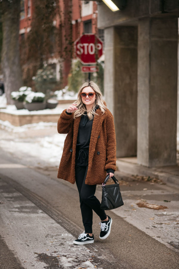 Chicago fashion blogger wearing a brown teddy coat with a black jogger sweatpants set and women's Vans sneakers.