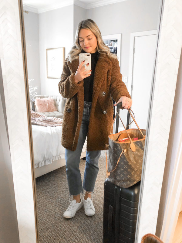 Travel blogger wearing a brown teddy coat and white leather sneakers with an Away suitcase.
