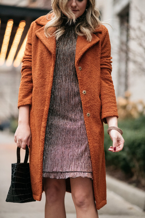 Fashion blogger wearing a sparkly dress with a teddy coat.