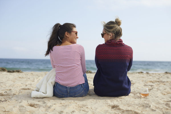 Bruntette in a red striped shirt and blonde in a blue and red fair isle funnelneck fleece on the beach.