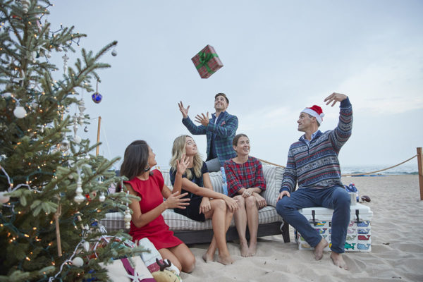 Dave Adams throwing a Christmas present in the air to John Philp Thompson while Jessica Sturdy and Liz Adams are on the couch on the beach.