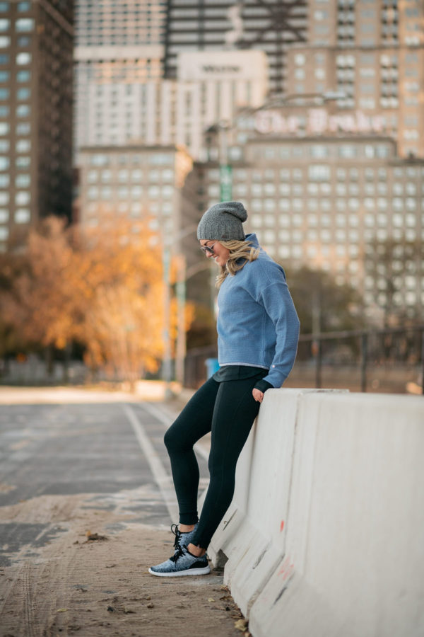 Chicago fitness blogger wearing Calia by Carrie Underwood workout clothing on the Lakefront Running Trail with the Drake Hotel in the background talking about health and wellness over the holidays.