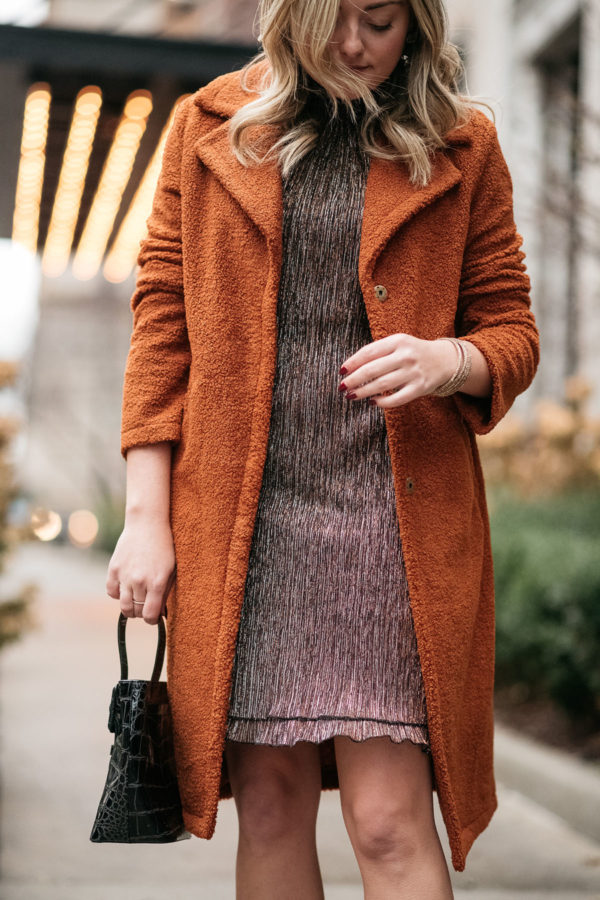 Outfit blogger wearing a brown teddy coat with a party dress.