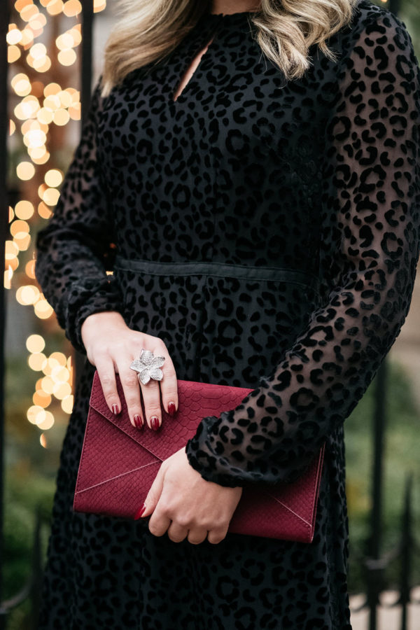 Fashion blogger Bows & Sequins styling a black velvet dress in a subtle leopard print with a burgundy clutch and a gorgeous rhinestone flower statement cocktail ring.
