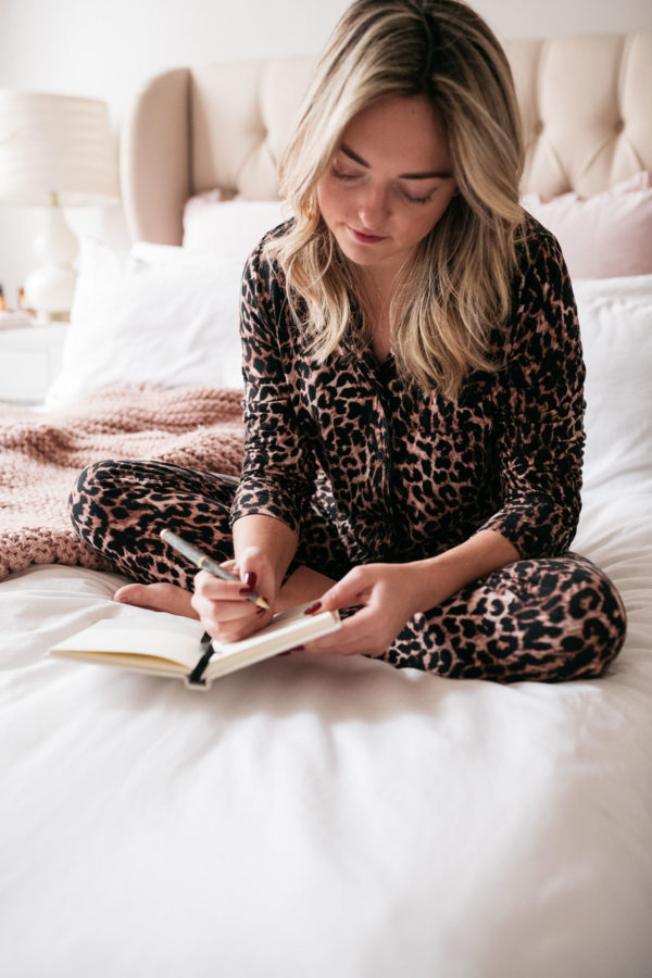 Woman wearing a leopard pajama set while sitting in bed journaling.