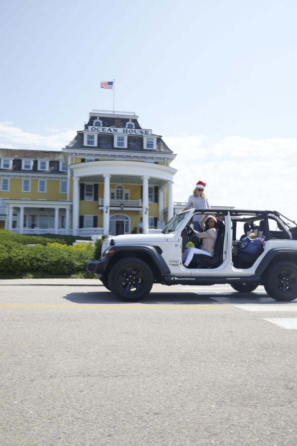 Jessica Sturdy and Caila Quinn driving a white Jeep in Santa hats in front of Ocean House Rhode Island.