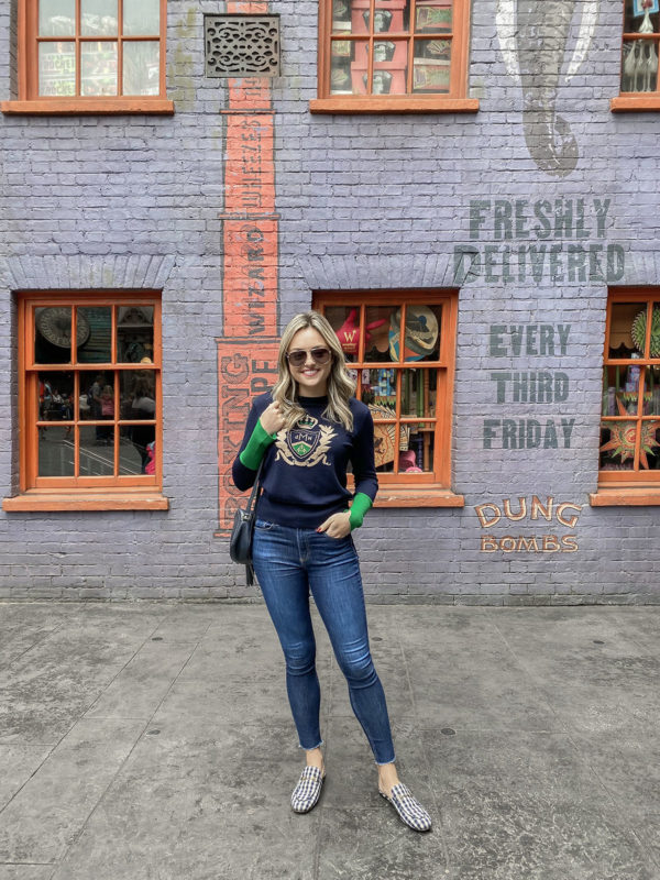 Travel blogger Jessica Sturdy wearing a DMN Paris Crest Sweater, rag & bone jeans, and Gucci gingham Princetown loafers at Universal Orlando.