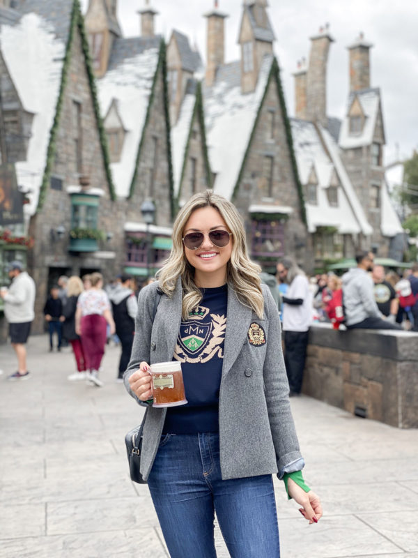 Travel blogger Jessica Sturdy of Bows & Sequins drinking Butterbeer at the Wizarding World of Harry Potter in Orlando, Florida at Universal Studios Islands of Adventure.