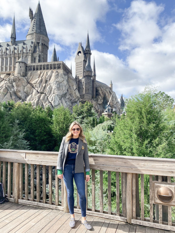 Travel blogger Bows & Sequins in front of Hogwarts Castle in Wizarding World of Harry Potter