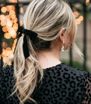 Fashion influencer Jessica Sturdy of Bows & Sequins wearing a black velvet hair bow with blonde curls.