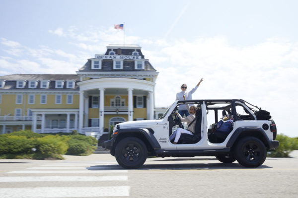Caila Quinn driving a white Jeep with Jessica Sturdy standing out of the sunroof in front of Ocean House in Watch Hill, Rhode Island.