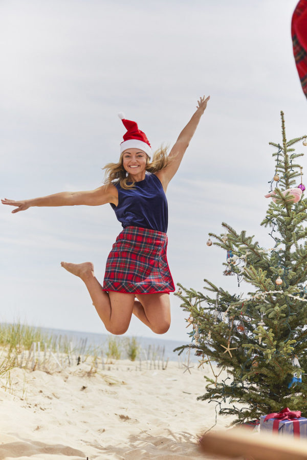 Preppy blogger Jessica Sturdy wearing a Santa hat and a Vineyard Vines plaid skirt jumping on the beach next to a Christmas tree.