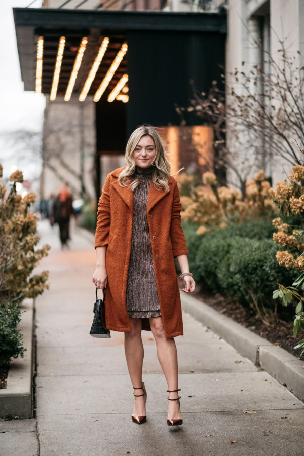 Chicago fashion influencer Bows & Sequins wearing a burnt orange teddy coat with a sparkly dress and copper pumps.
