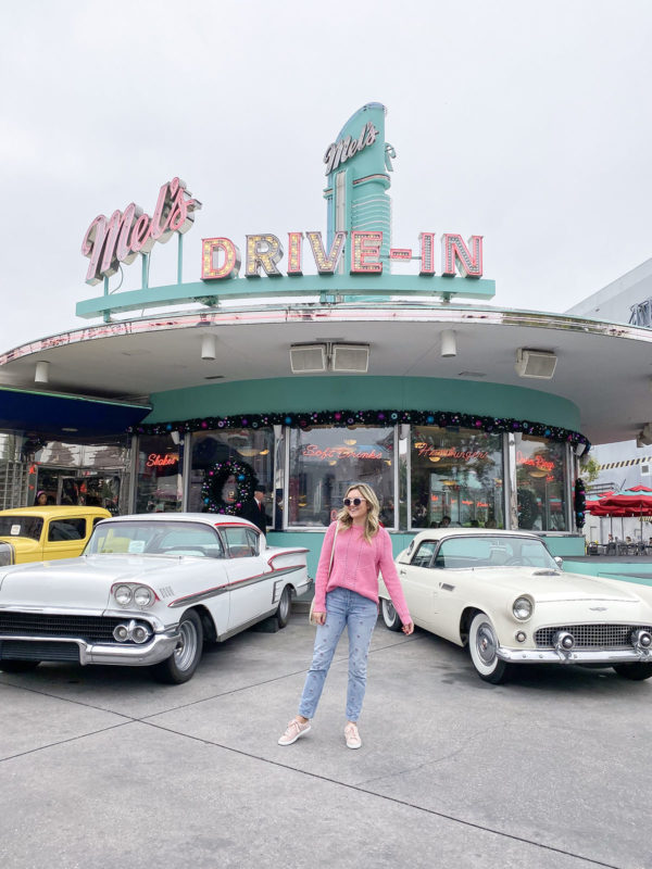 Travel blogger Bows & Sequins in front of Mel's Drive In at Universal Orlando