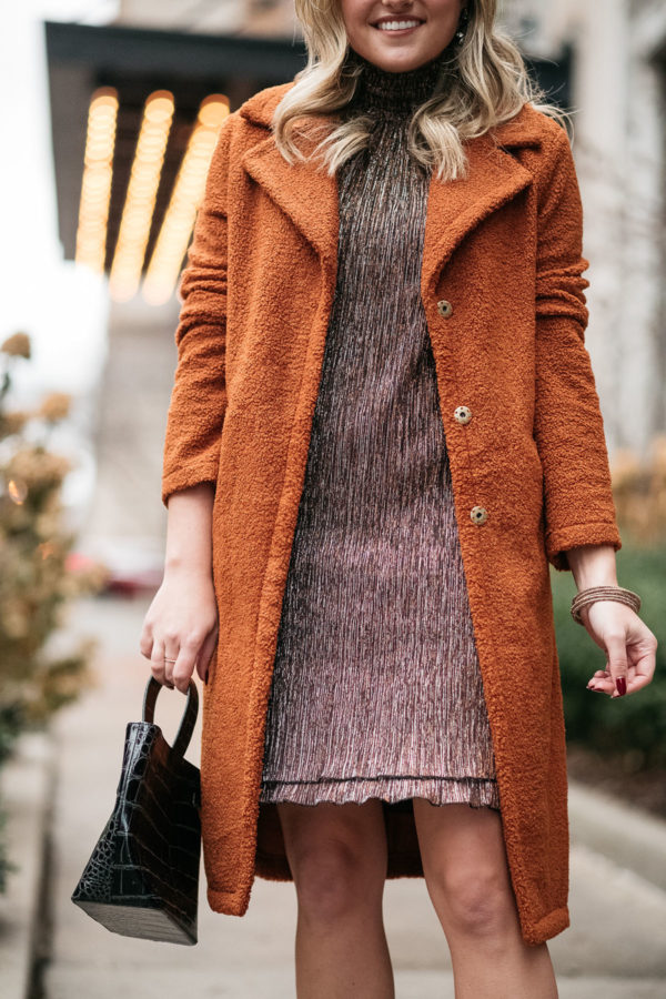 Lifestyle blogger wearing a shimmery dress with a teddy coat for the holidays.