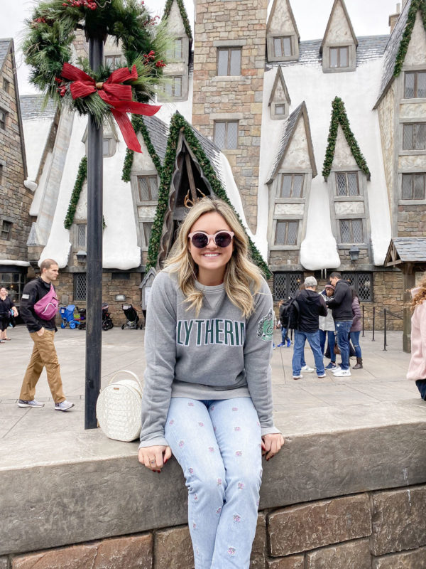 Travel blogger Bows & Sequins at the Wizarding World of Harry Potter wearing a Slytherin sweatshirt.