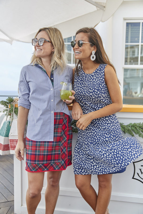 Bows & Sequin wearing a blue and white striped button down shirt halfway tucked in to a plaid skirt standing next to Caila Quinn wearing a printed Vineyard Vines dress at the Veuve Clicquot bar at Ocean House.