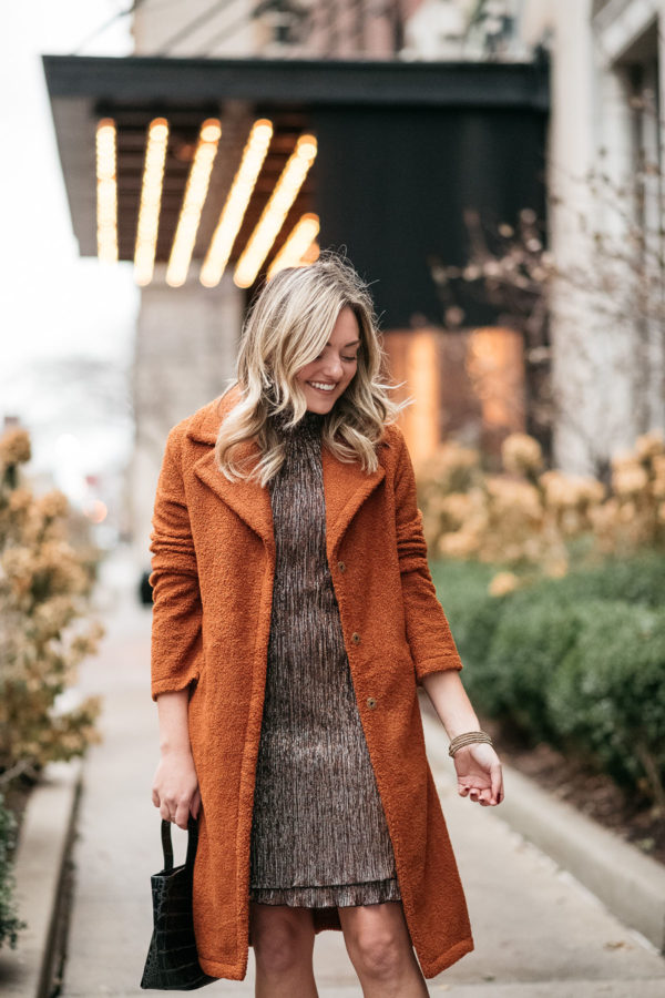 Fashion and beauty blogger wearing a shimmery copper and silver dress with a teddy coat for the holidays.