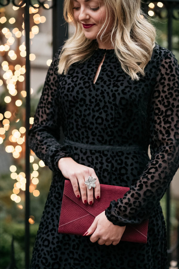 Fashion blogger wearing a black velvet dress in leopard print with a crystal flower statement ring and a burgundy suede clutch.