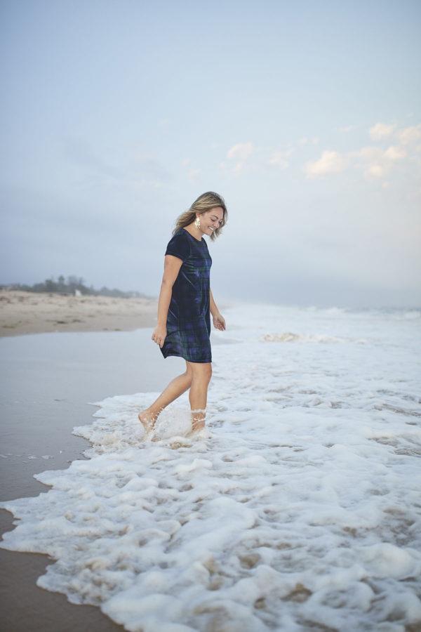Pretty fashion blogger Bows & Sequins wearing a Vineyard Vines Plaid Velvet Dress in the ocean.