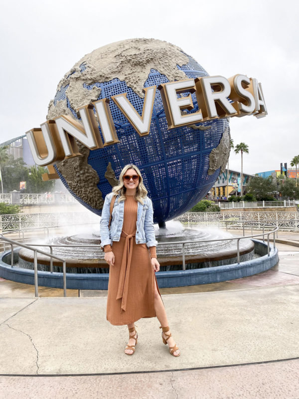 Travel blogger Jessica Sturdy of Bows & Sequins styling a Topshop Tie-Front Midi Dress with cognac suede sandals, Quay sunglasses, and a denim jacket.