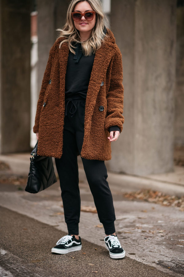 Casual fashion blogger Jessica Sturdy of Bows & Sequins wearing a teddy coat with a jogger set and women's Vans sneakers.