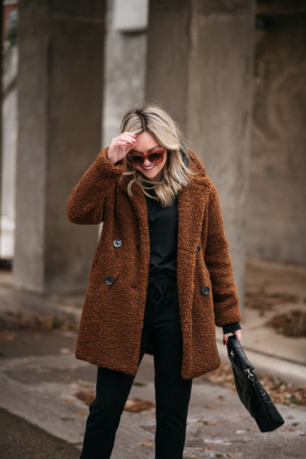 Chicago influencer Bows & Sequins wearing Quay sunglasses, a Zara handbag, a brown teddy coat, and a Vineyard Vines jogger set.