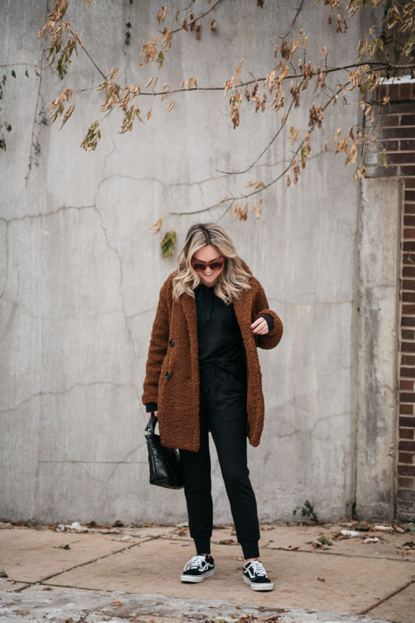Fashion blogger wearing a matching black hoodie and joggers set with a brown fuzzy coat and Vans.