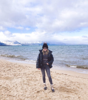 Travel blogger Jessica Sturdy of Bows & Sequins wearing a Nanushka Leather Puffer Coat, See by Chloe Logo Turtleneck, Grey Skinny Jeans, Black Fur Beanie, and Marc Fisher Shearling Booties by Lake Tahoe on the sand with snowy mountains in the back.