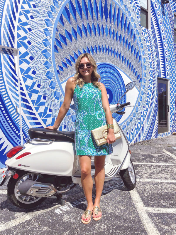 Jessica Sturdy wearing Lilly Pulitzer in Palm Beach in front of a white Vespa and blue and white printed wall mural.