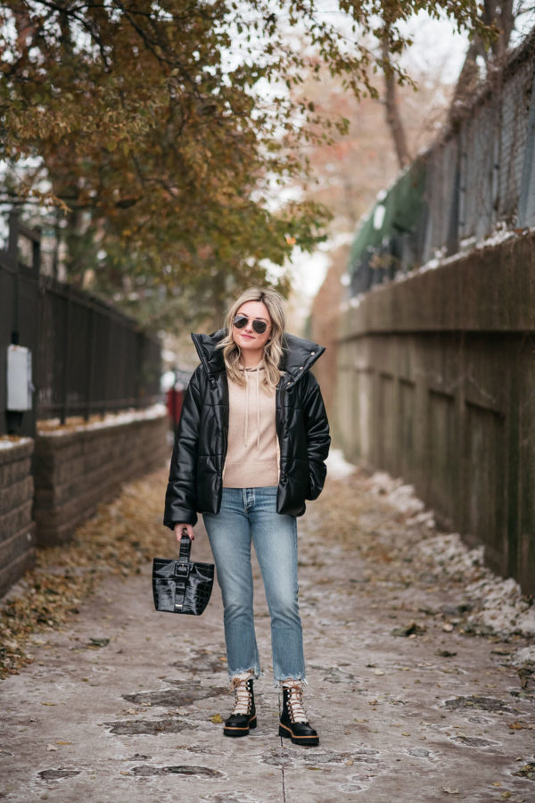 Chicago style blogger Bows & Sequins wearing a puffy leather jacket with a camel cashmere hoodie, raw hem cropped jeans, and leather shearling hiking boots.