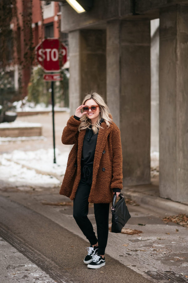 Chicago travel blogger wearing a teddy coat with a comfy cozy jogger set for a cute travel day outfit with Vans sneakers.