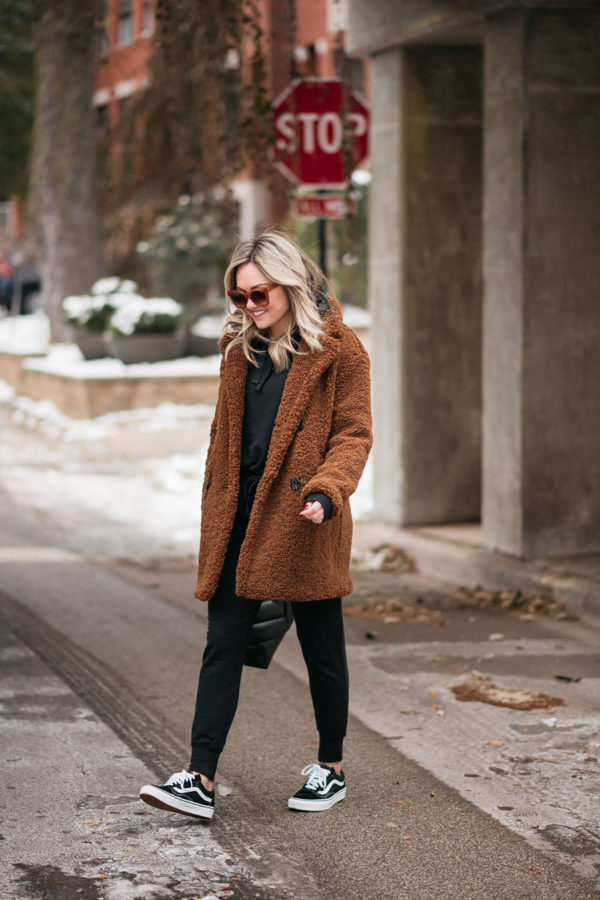 Fashion blogger Jessica Sturdy of Bows & Sequins wearing a teddy coat with black joggers and classic Vans.