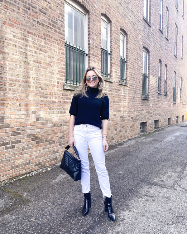 Chicago blogger Jessica Sturdy of Bows & Sequins styling white cropped straight leg jeans with black booties, a sweater, and silver accessories.