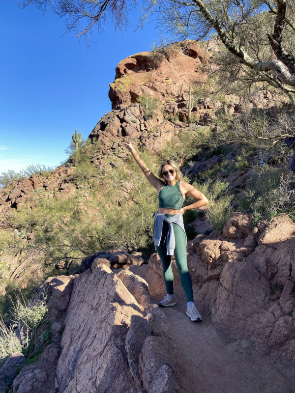 Fitness blogger Jessica Sturdy wearing a green Outdoor Voices Crop Top and Leggings while hiking Camelback Mountain in Phoenix, Arizona.
