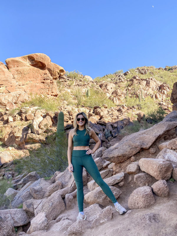Travel blogger Jessica Sturdy wearing a green Outdoor Voices Set while hiking Echo Canyon Trail in Scottsdale, Arizona.