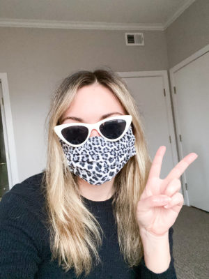 Fashion blogger taking a selfie wearing a face mask.