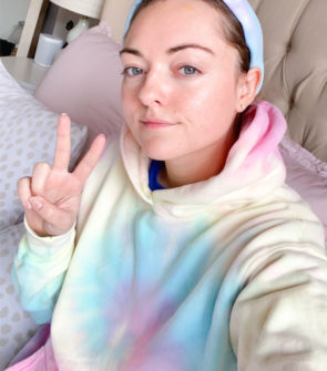 Fashion blogger wearing Dannijo tie dye sweatshirt at home with a matching Lele Sadoughi tie dye headband,
