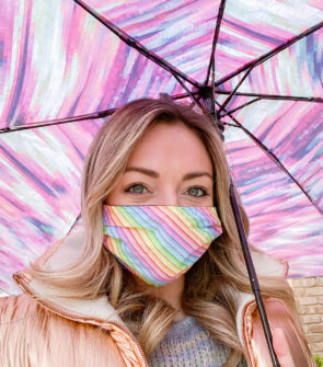 Lifestyle blogger Jessica Sturdy of Bows & Sequins wearing a rainbow face mask under a colorful umbrella.